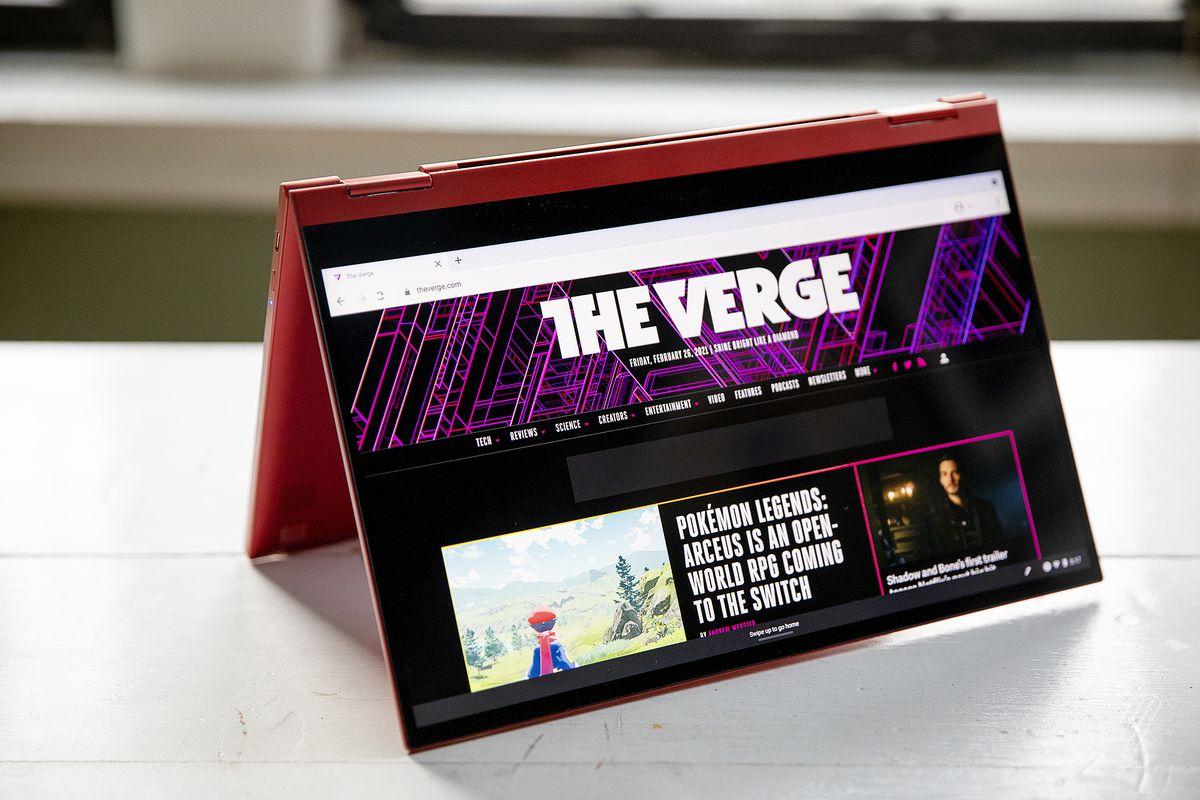O Samsung Galaxy Chromebook 2 no modo tenda, inclinado para a direita, com a tela voltada para a câmera.  A tela exibe a página inicial do The Verge.