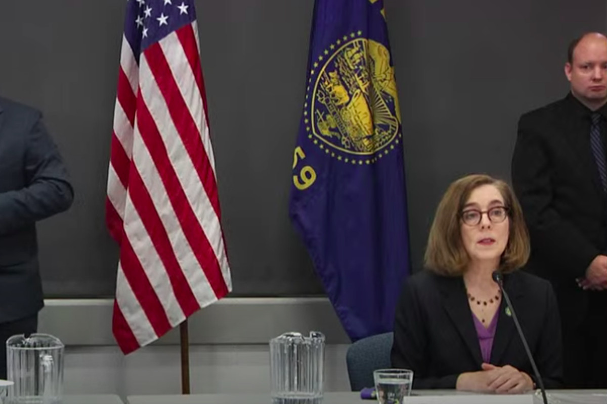 Kate Brown sits at a table with someone signing next to her.
