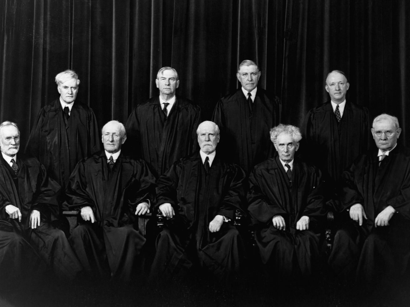 The justices of the Supreme Court for the 1937-38 term. Sitting, from left to right, Justices Sutherland and McReynolds, Chief Justice Hughes, Justices Brandeis and Butler. Standing, left to right, Justices Cardozo, Stone, Roberts, and Black.