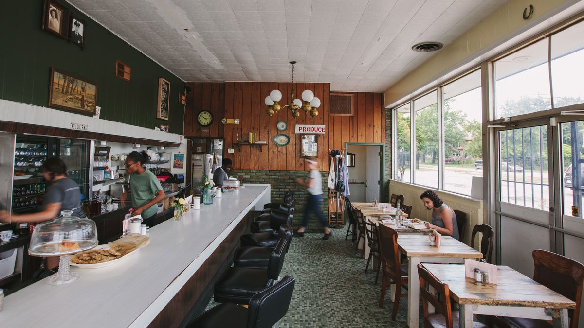 A green and wood-paneled diner restaurant with a lunch counter and kitchen staff standing behind the bar.