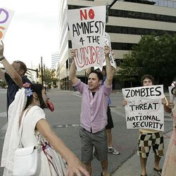 """Zombie Walk participants and """"zombie protesters"""" stroll the streets of Salt Lake City on Sunday."""