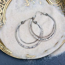 """<a href=""""https://mushmina.myshopify.com/collections/jewelry/products/crescent-hoops-silver"""">Silver Crescent Hoops</a>, $75—$96"""
