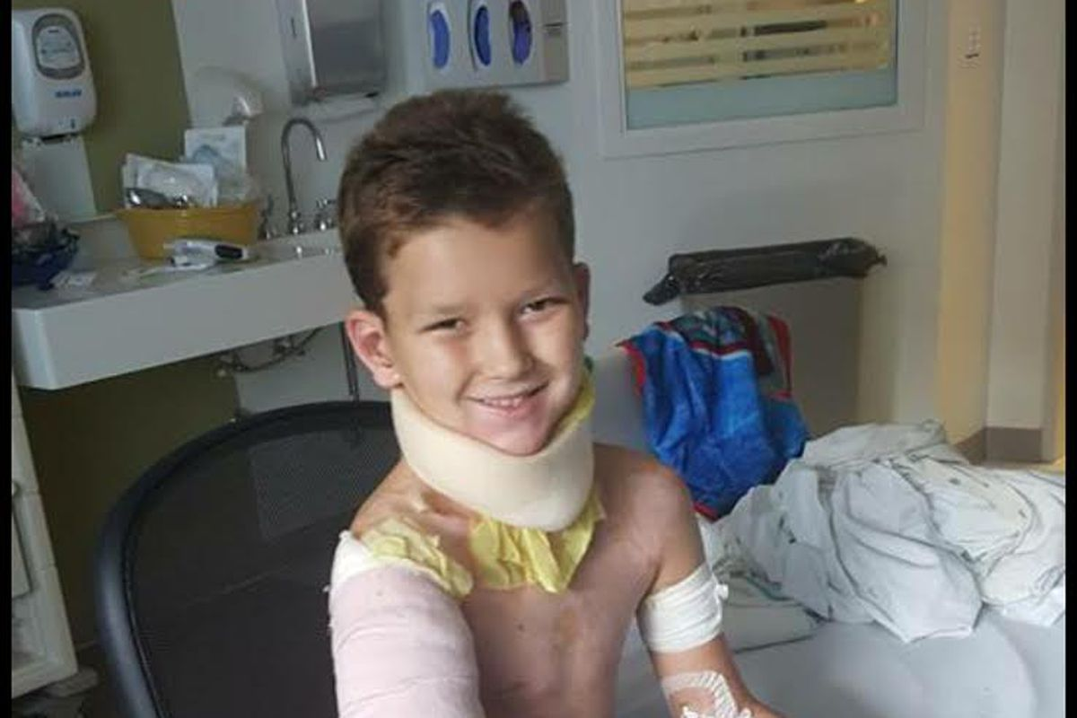 A child sits on a chair next to a hospital bed. He has caucasian skin and sandy-brown hair. He is smiling, but he is wrapped in hospital dressings: a large white collar on his throat, an Ace bandage over gauze on his right upper arm, a dark brown glove on