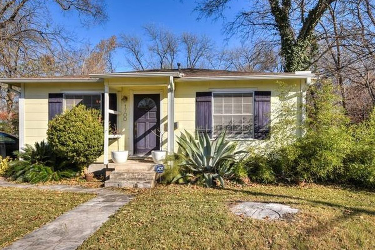 Small, one-story yellow frame house with light yellow walls, black shutters small covered front porch, yard and agave/shrubs in winter