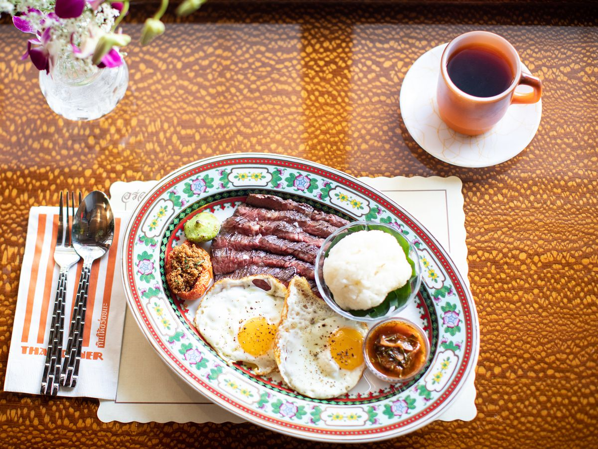 An oval shaped plate of food with sunny side up eggs, thinly sliced steak, a bowl with white rice, and bowl with an orange sauce