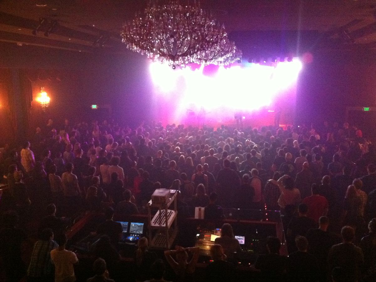 The interior of El Rey Theatre. There are many people in the audience viewing a show. On the stage are lights. Hanging above the audience are multiple large chandeliers.