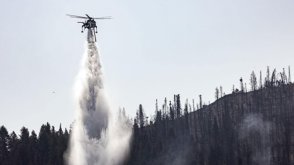 A helicopter drops water on hot spots as crews fight the Parleys Canyon Fire near Park City on Monday, Aug. 16, 2021.