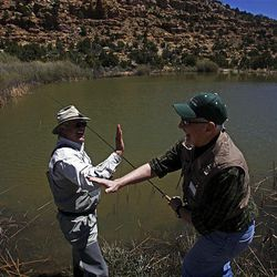 Cancer patient Michael Pickens, right, gives retreat volunteer John Kern a high-five after catching a fish during the Reel Recovery fly-fishing retreat for cancer patients, at Falcon's Ledge lodge near Altamont.