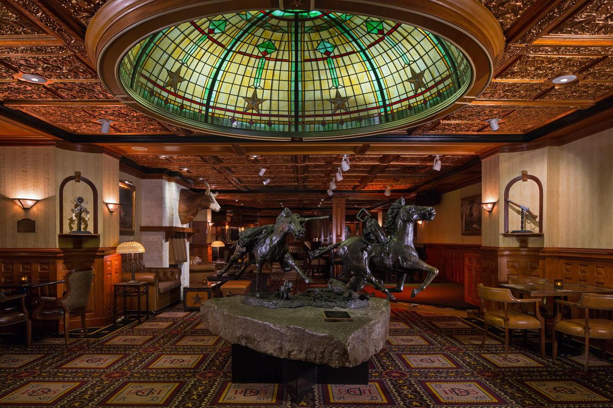 The interior of the Driskill Hotel lobby in Texas. There is a large sculpture of multiple horses in the center of the lobby. Above the sculpture is a stained glass domed ceiling. The ceiling is gilded bronze.