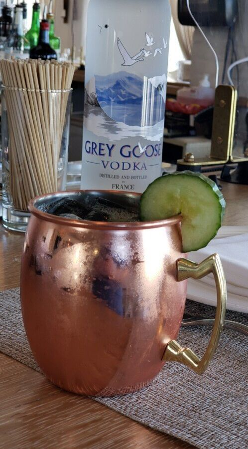 A cocktail in a copper mug with a slice of cucumber