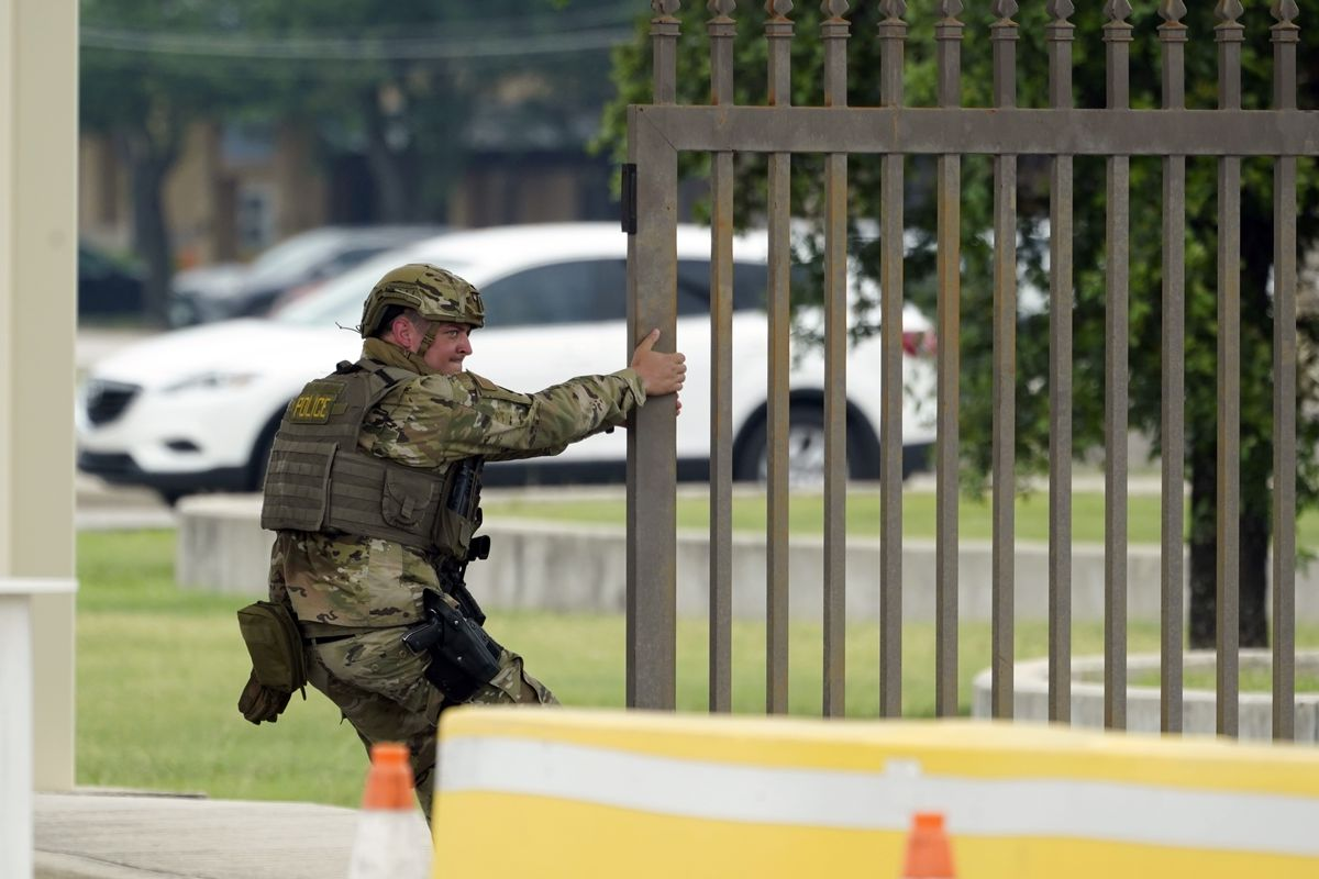 A military policeman closes a gate at JBSA-Lackland Air Force Base, Wednesday, June 9, 2021, in San Antonio. The Air Force was put on lockdown as police and military officials say they searched for two people suspected of shooting into the base from outside.
