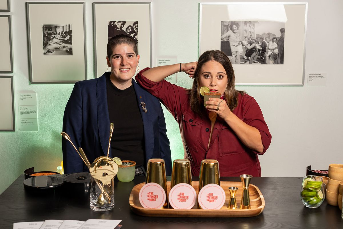 Lauren Amador and Danielle Gavaldon stand behind a bar table holding shakers and coasters. Gavaldon sips a drink and has her elbow on Amador's shoulder.