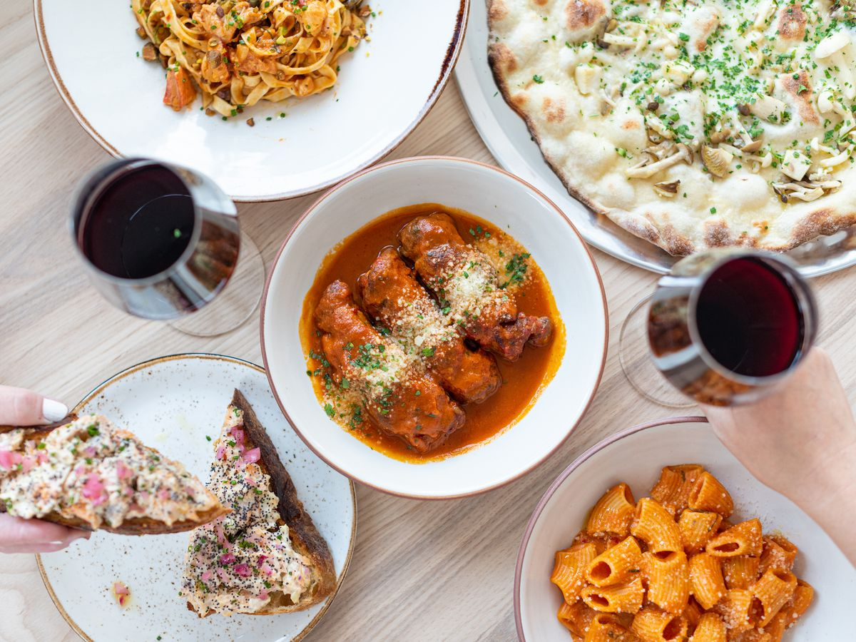 A full plate of Italian food including wine and pasta, shown from above.