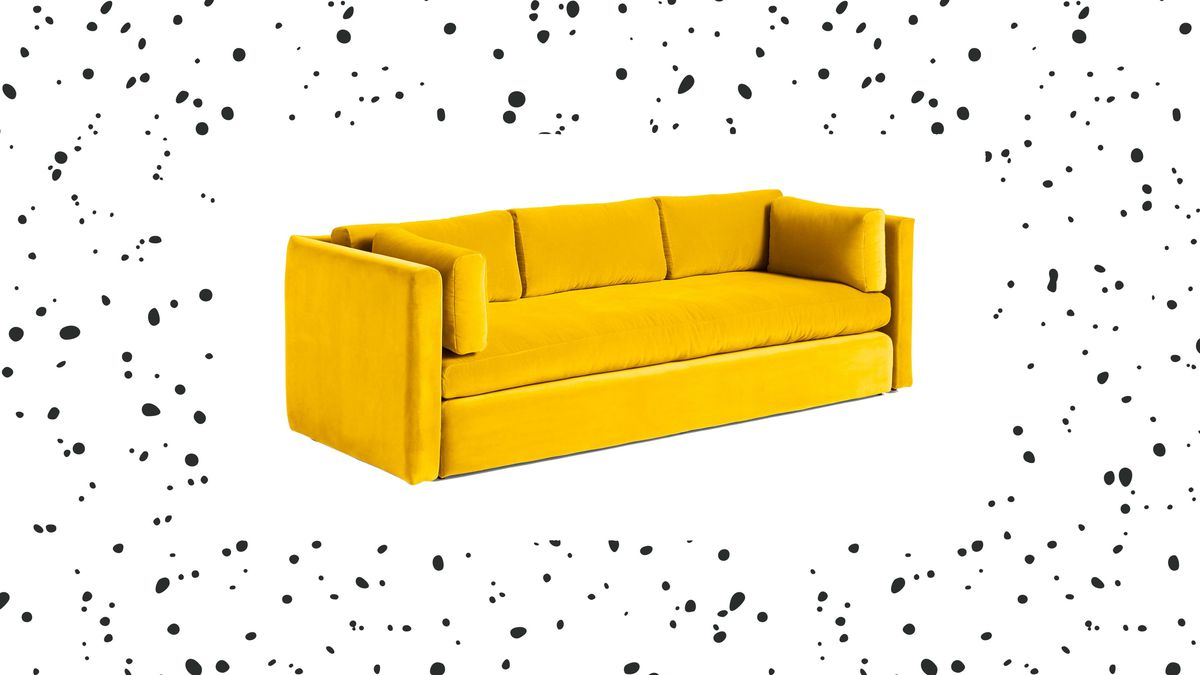 Yellow velvet couch on white background with black dot pattern.