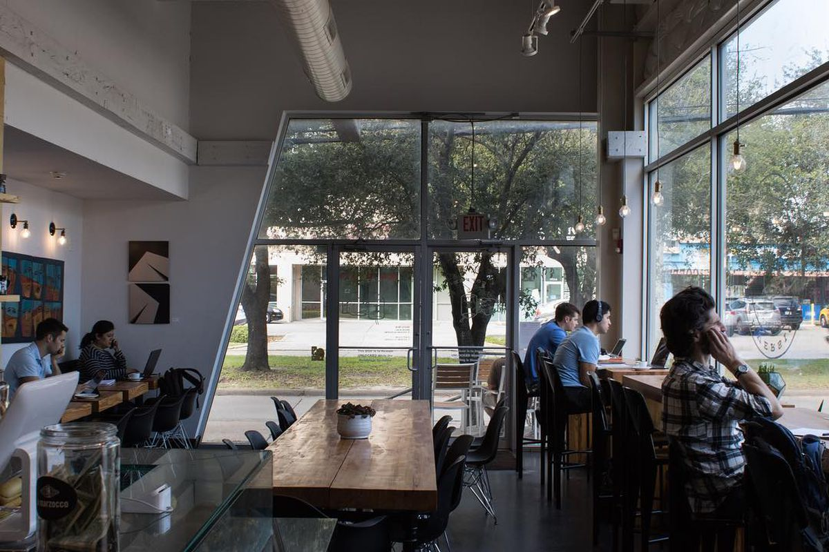 a window-heavy coffee shop with people sitting at counters