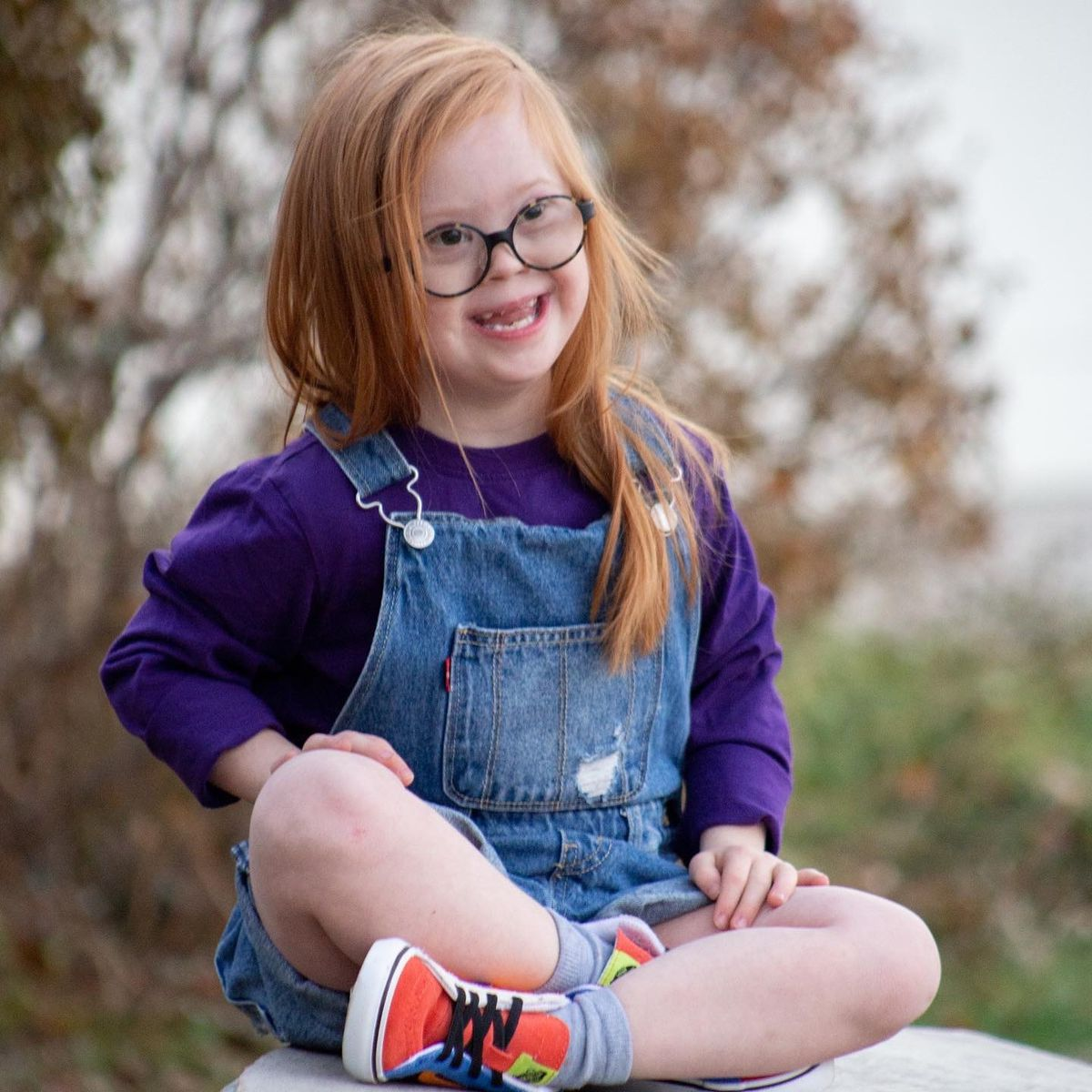 A little girl with Down syndrome smiles at the camera. She is sitting cross-legged outside. She is wearing glasses, jean overalls and a purple shirt.