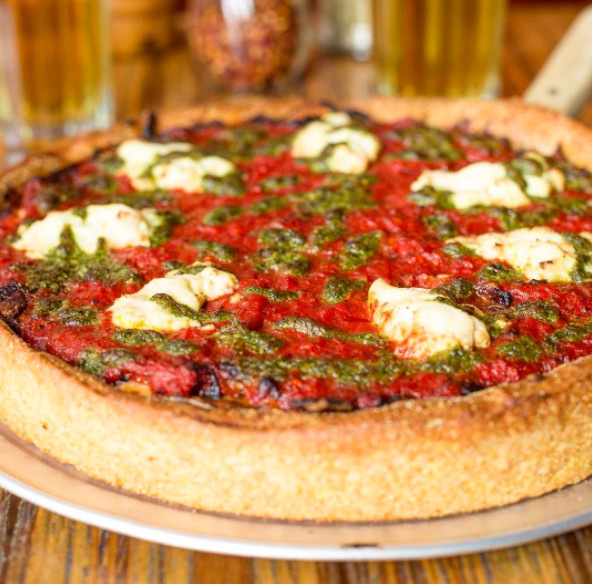 thick crust pizza topped with tomato, cheese and pesto