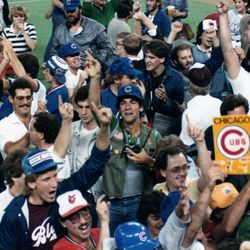 """A scrum of fans and media on the field. Look closely just to the right of the """"Chicago Cubs"""" sign -- you'll see former Channel 2 sportscaster Johnny Morris lost in the crowd"""