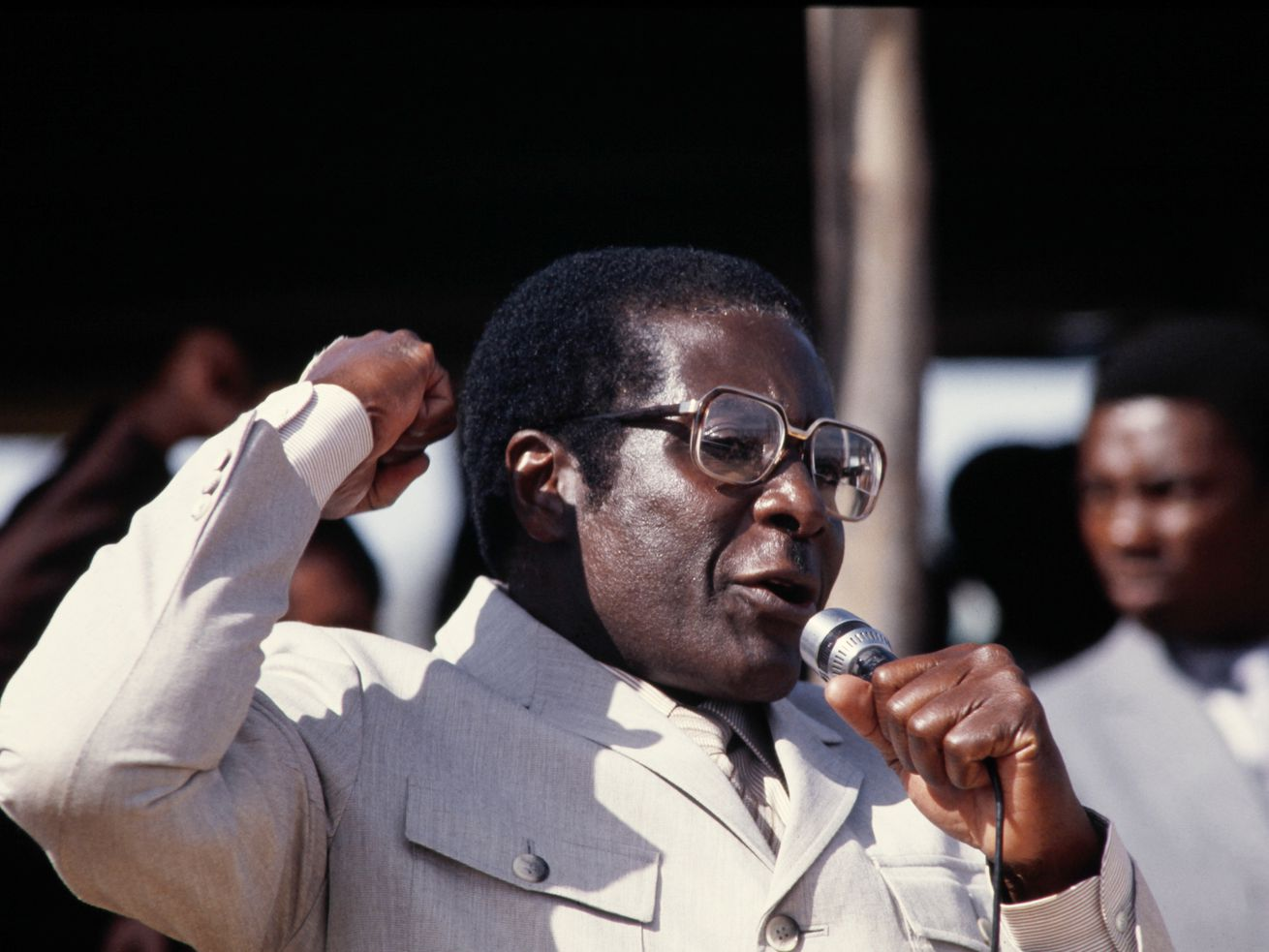 Zimbabwean Prime Minister Robert Mugabe holding a microphone in one hand and making a fist with the other while speaking to a crowd in 1984.