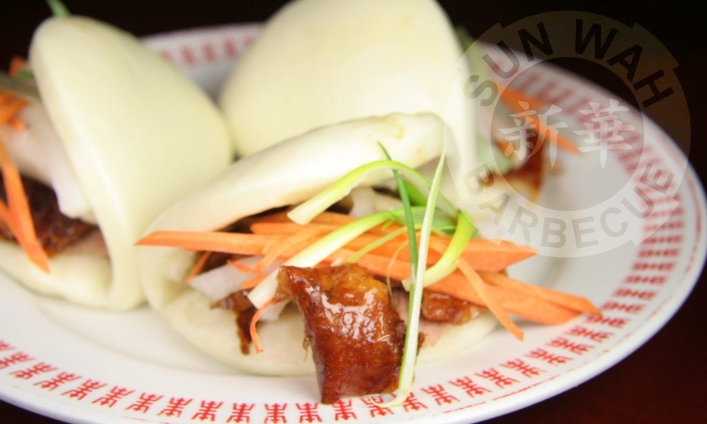 A plate of baos filled with duck skin and garnishes.