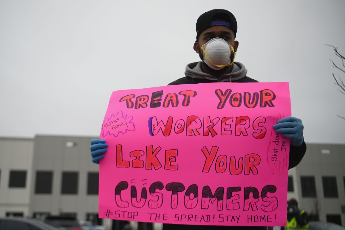 """An Amazon warehouse worker stands outside and  holds a sign that reads """"Treat your workers like your customers."""""""