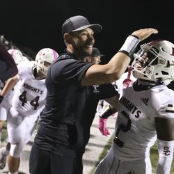 Lone Peak's Luke Hyde celebrates with a coach as their team's win against Corner Canyon looks imminent at Corner Canyon High School in Draper on Thursday, Oct. 7, 2021.