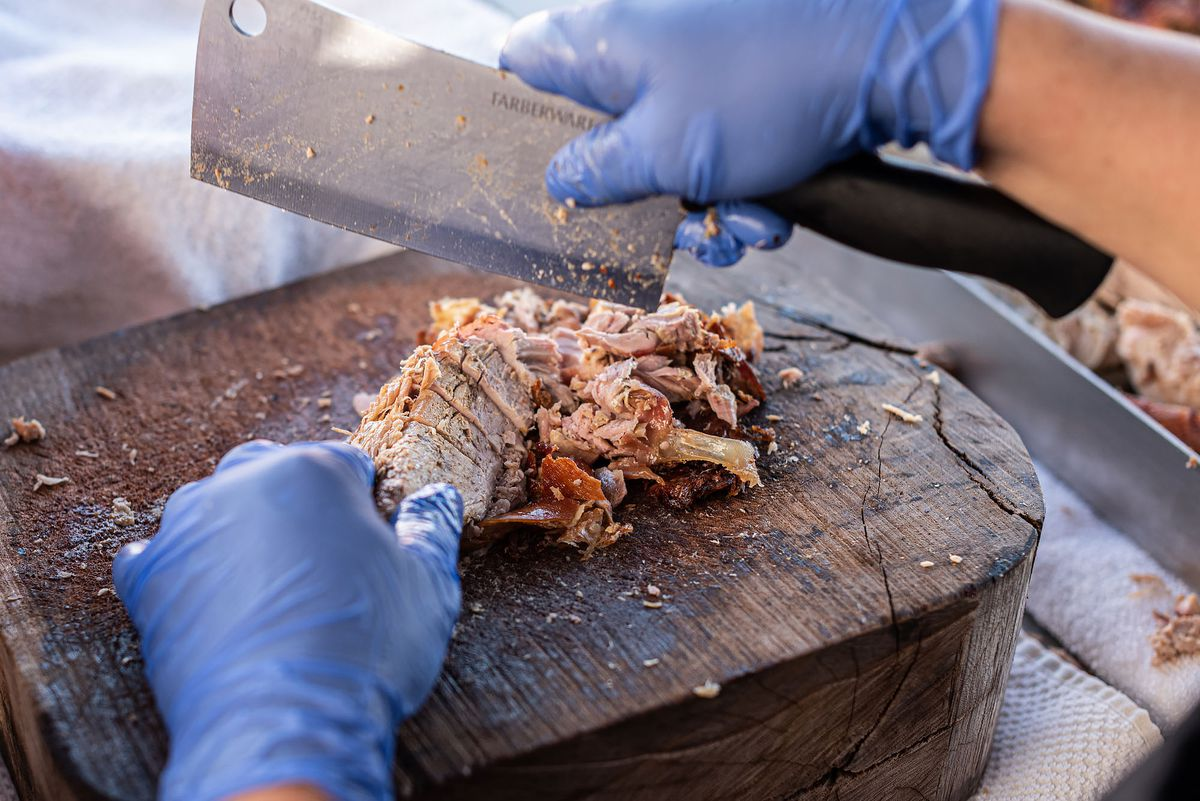 A large cleaver works over pork for upcoming tacos, on a wooden cutting board.