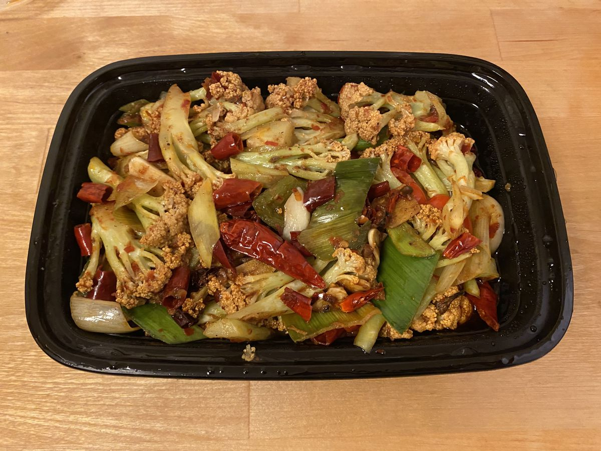 A black takeout container filled with cooked cauliflower, peppers, and onions, tossed in a spicy hot oil