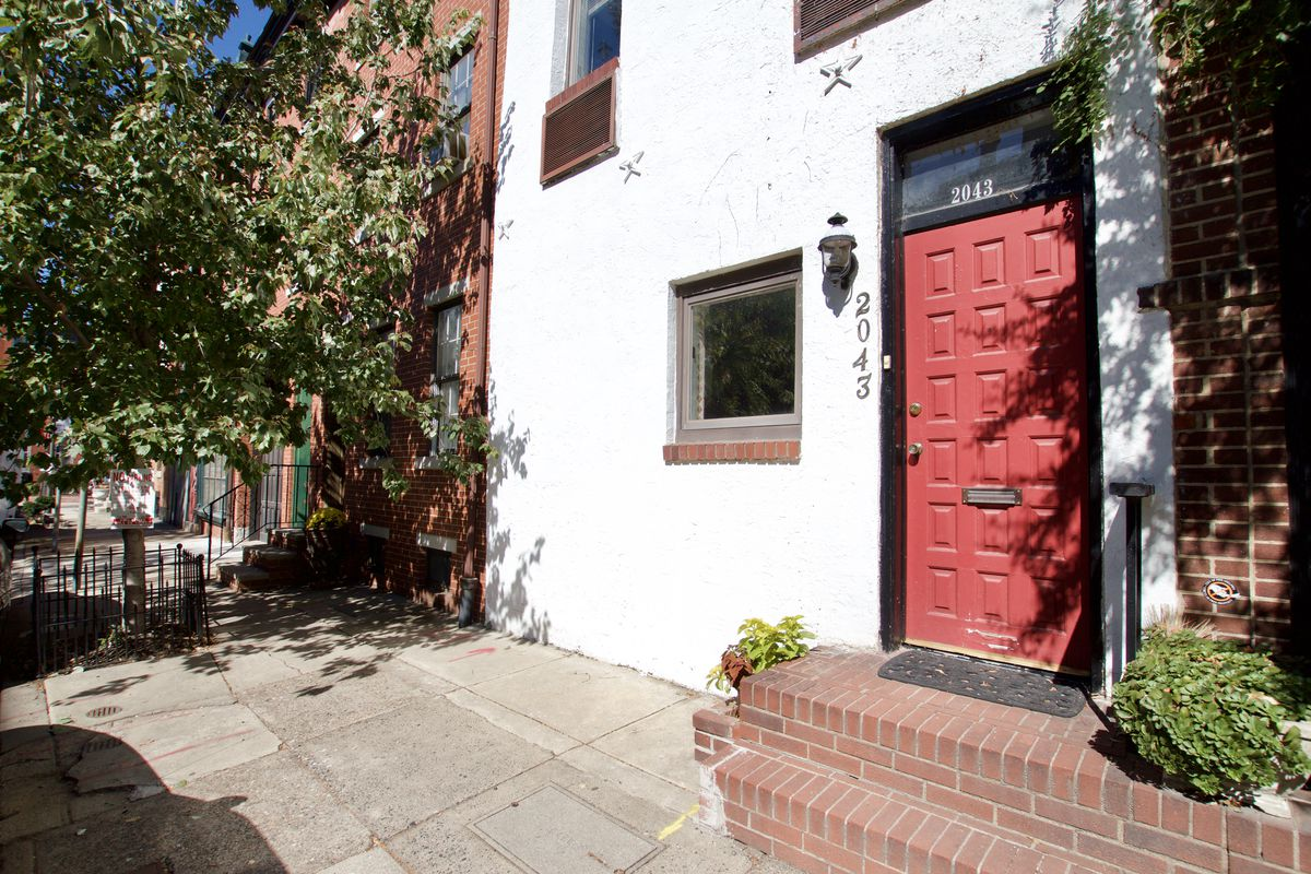 A white stucco home in Philadelphia's Rittenhouse Square neighborhood with a red door.