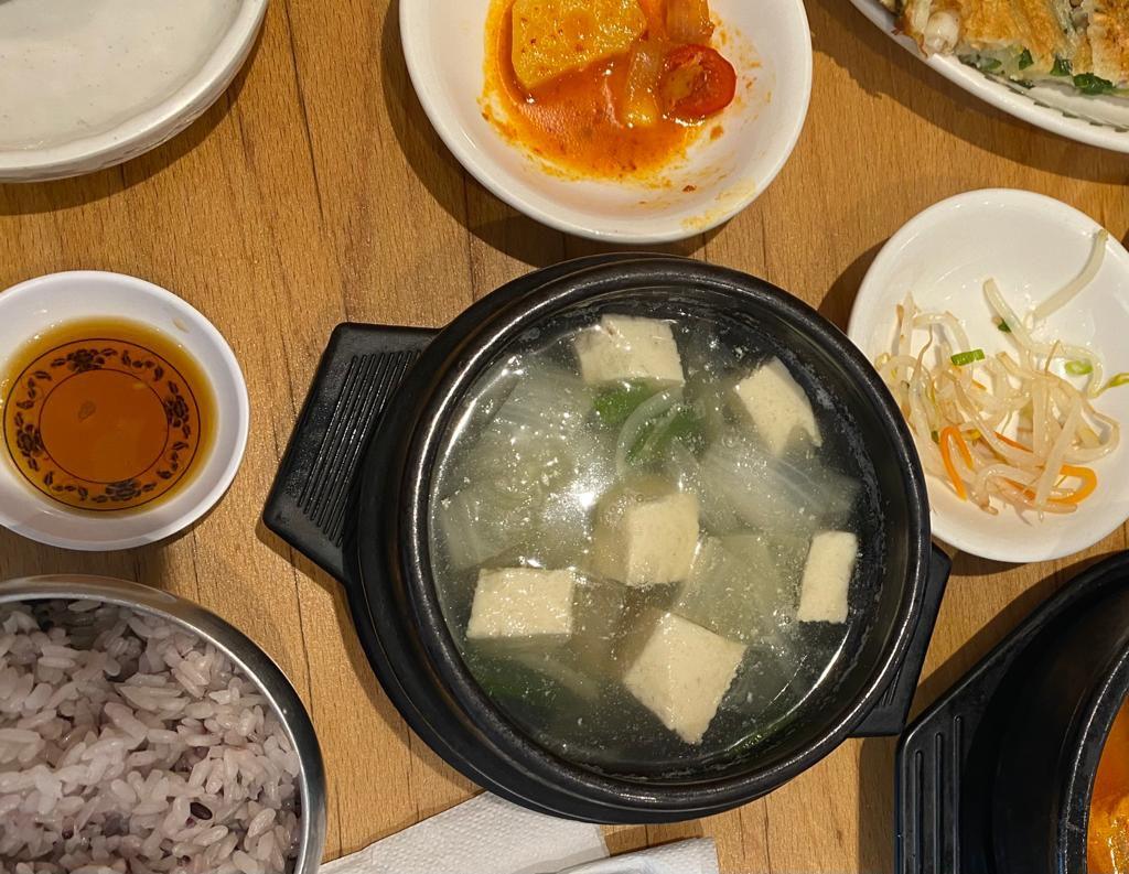Soondubu jjigae with banchan on a table
