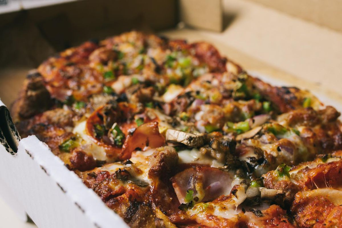 A pizza from Slim and Husky with pepperoni, cheese, spinach, red onions, sausage, and mushrooms