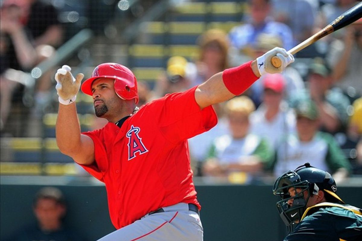 Los Angeles <strong>Angels</strong> first baseman <strong>Albert Pujols</strong> hits an RBI double <strong>in the first inning</strong> against the Oakland Athletics during a spring training game at Phoenix Municipal Stadium.
