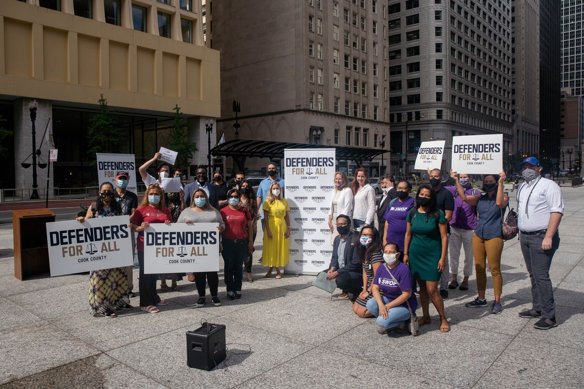 Public officials and community organizers pose for a photo after a press conference outside the Richard J. Daley Center Wednesday morning, July 22, 2020.