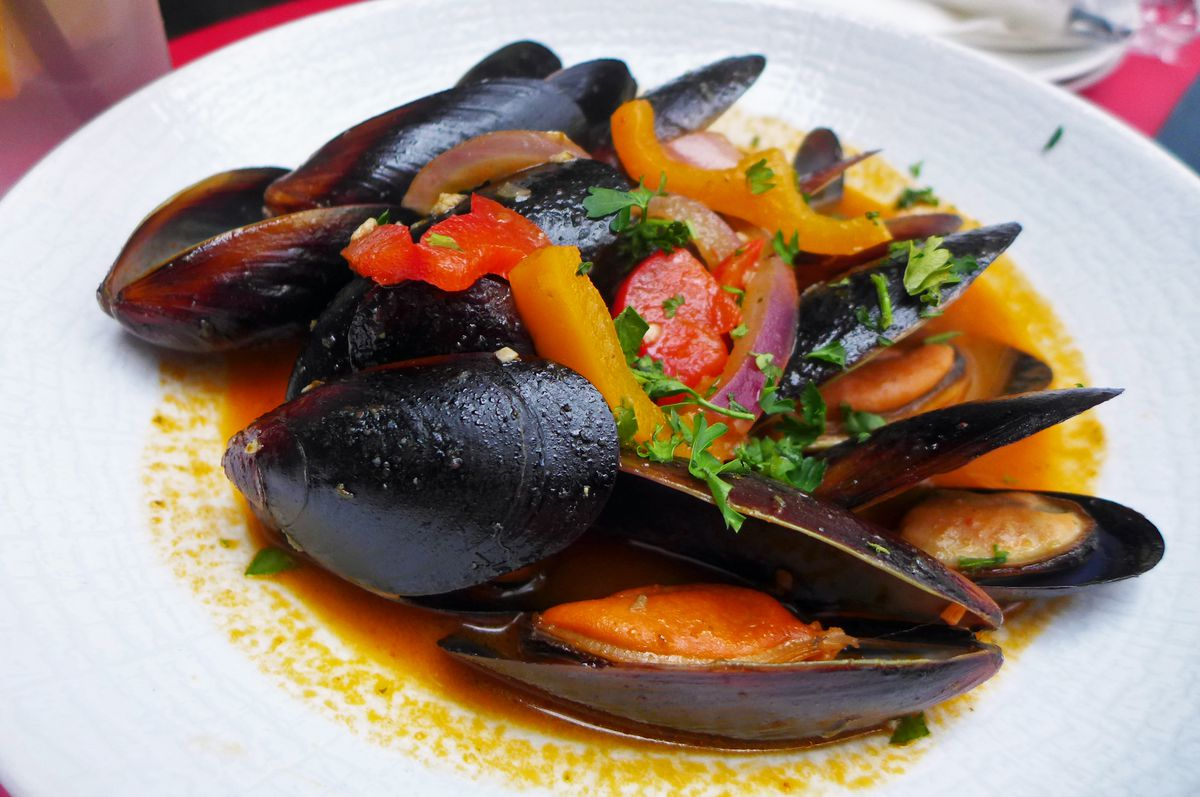 Mussel in their shells in a red sauce and white bowl, with yellow and red strips of pepper on top.