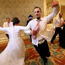 Chaya Zippel dances with her brother, Mendy Zippel, during a traditional Chabad Lubavitch Jewish wedding at the Grand America Hotel in Salt Lake City on Monday, Sept. 12, 2016. Men and women celebrate separately, with the exception of one song with their siblings and parents.