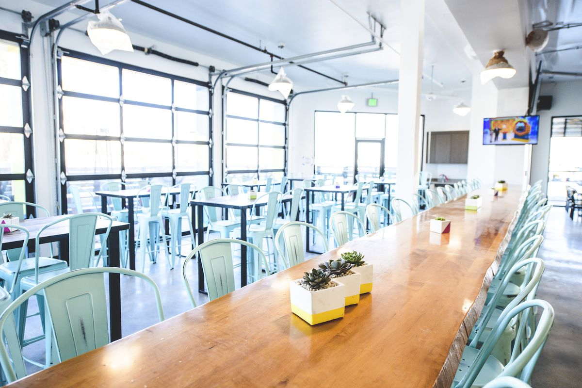 A light, sunny brewpub with roll up doors and long tables.