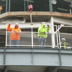 A section of fence being fitted, along the back of the bleacher patio level -