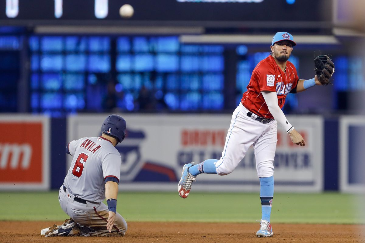 Miami Marlins shortstop Miguel Rojas (19) takes out Washington Nationals catcher Alex Avila (6) and throws to first base against the Washington Nationals during the sixth inning at loanDepot Park.