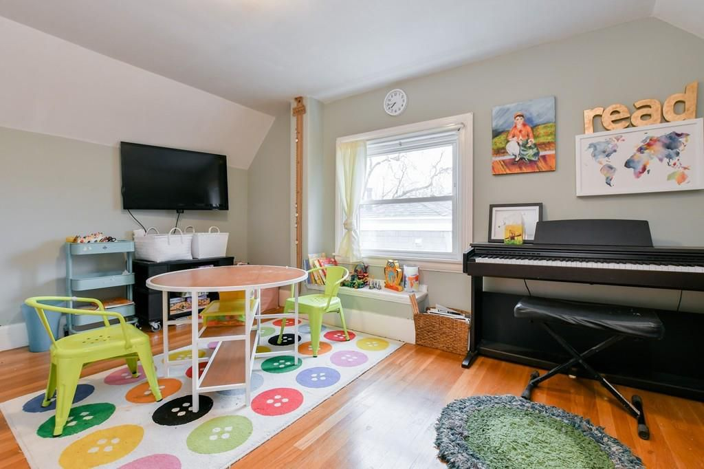 A room with a kids table and chairs next to an electric keyboard.