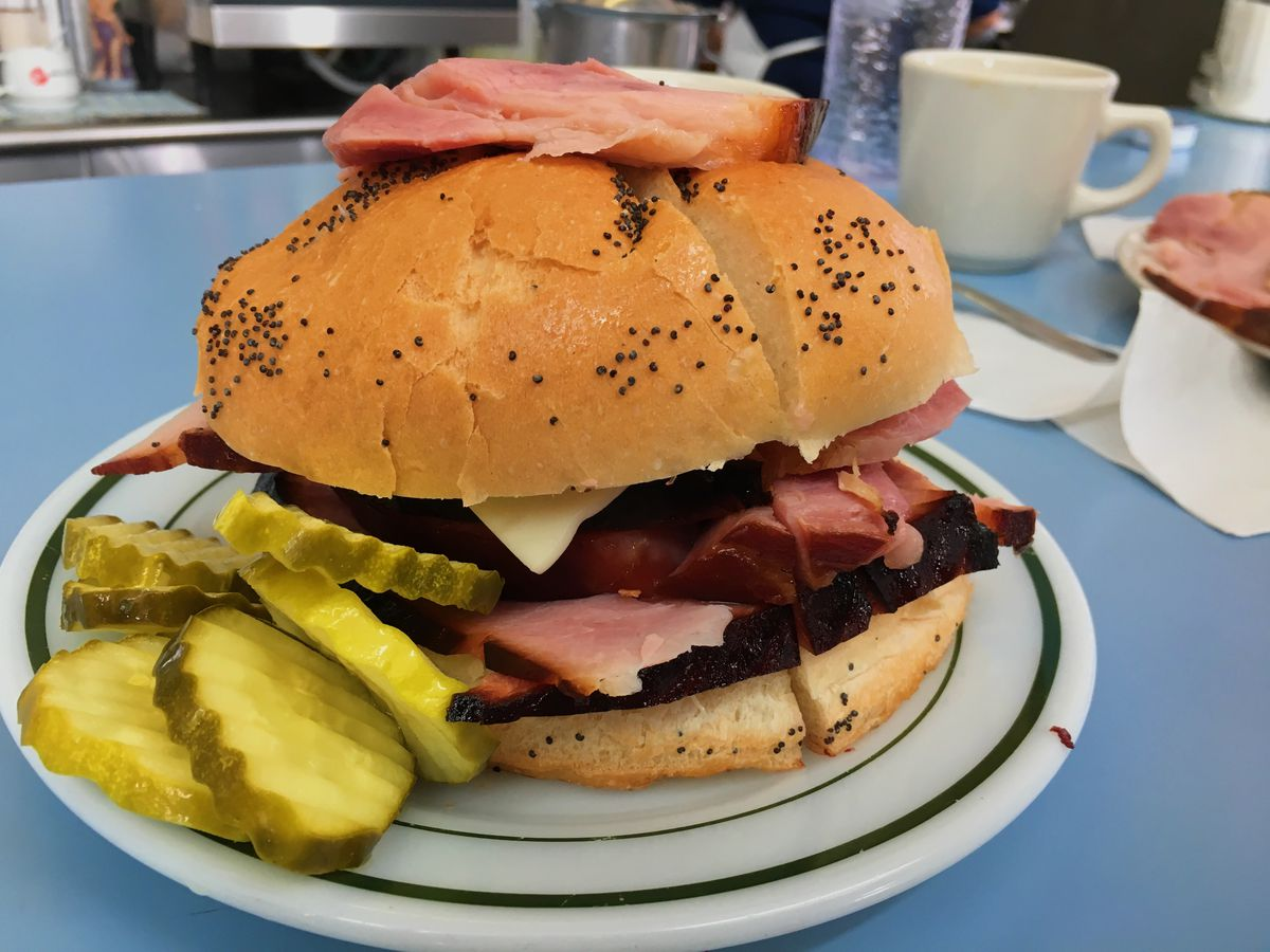 A large ham sandwich on a bun with poppy seeds. It has a slice of ham on top of the bune and a pile of pickles on the side
