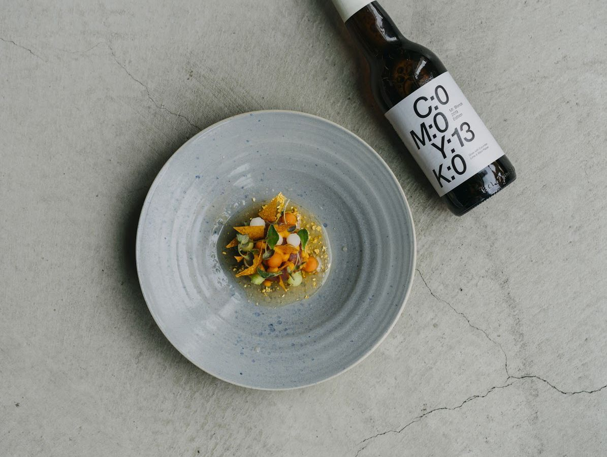 As seen from above chunks of tuna and carrot sit in a speckled broth on a small plate beside a bottle of craft beer.