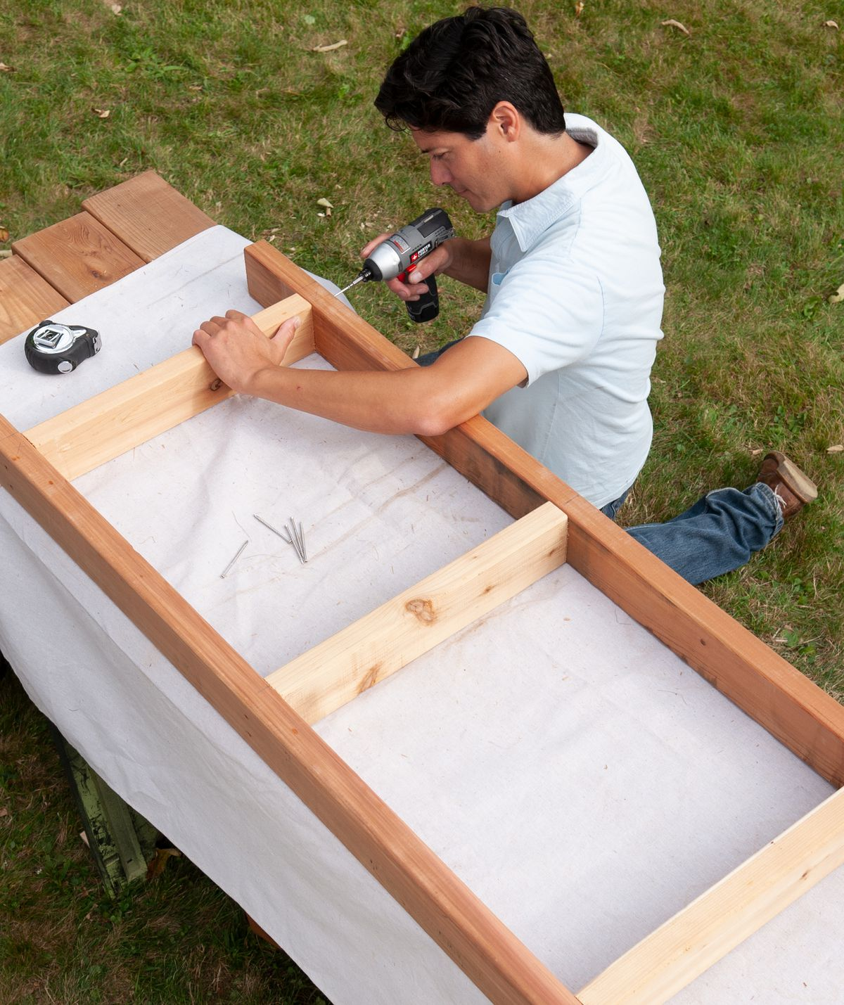 Man Cuts And Assembles Seat Base Of Arbor Bench