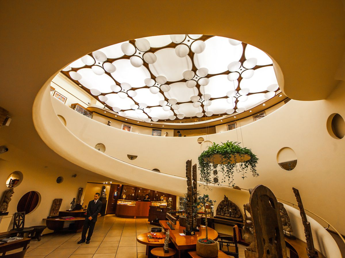 V.C. Morris Gift Shop by Frank Lloyd Wright. The interior has a curved staircase and a circular skylight with an ornamental design.
