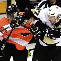 Pittsburgh Penguins' Sidney Crosby, right, shoves his glove and stick into the face of Philadelphia Flyers Brayden Schenn during a multi-fight brawl in front of the benches during the third period of Game 3 in a first-round NHL Stanley Cup playoffs hockey series, Sunday, April 15, 2012, in Philadelphia. The Flyers' 8-4 win puts them ahead 3-0 in the series. (AP Photo/Tom Mihalek)