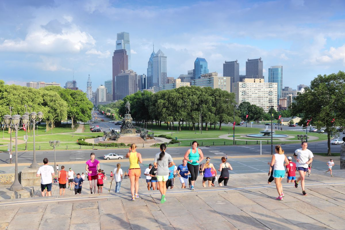 Young people running up and down the Rocky steps with Philly skyline in the background.