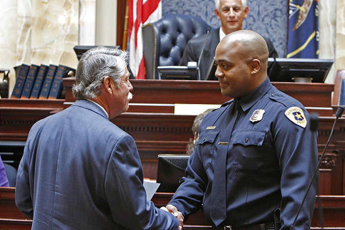 Sen. Gene Davis shakes hands with Salt Lake City police officer Uppsen Downes as the Senate honors him for stopping a gunman near the Grand America Hotel in August.
