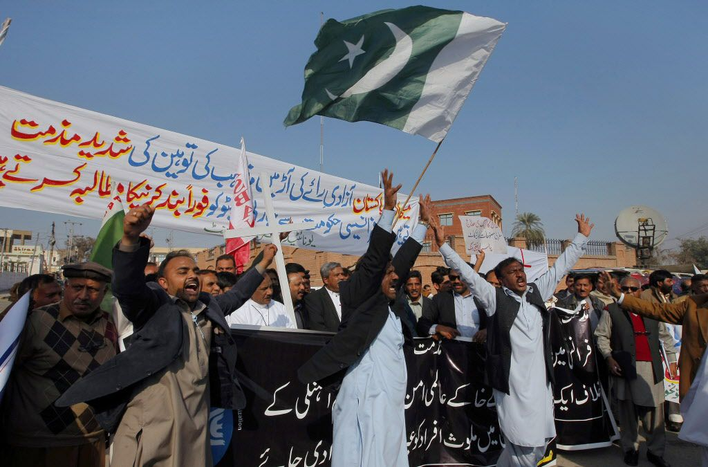 """Members of United Christian Movement chant slogans during demonstration against caricatures published in the French magazine Charlie Hebdo, in Peshawar, Pakistan on Sunday. The banner on top reads, '""""Pakistani Christians condemn targeting religion in the"""