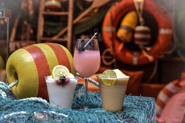 A trio of frozen cocktails are presented on a background filled with nautical decor
