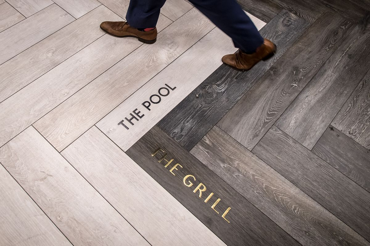 An image of flooring with a man walking above tiles that read the pool and the grill that are placed at a ninety degree angle.