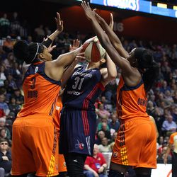Washington Mystics' Stefanie Dolson (31) tries to take a shot over the double-team of Connecticut Sun's Kelsey Bone (3) and Chiney Ogwumike (13).